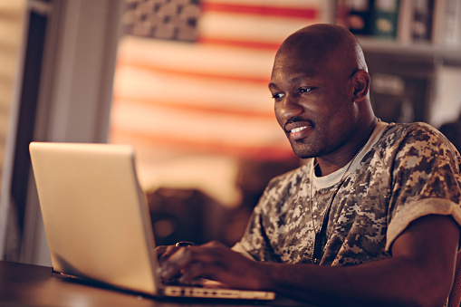 Picture of a young smiling african american male soldier sitting by a desk writing on his laptop. In the background is a bookshelf and on the wall is hanging an american flag. The soldier look tired but happy. From the left a dim light is sipping threw the window.
