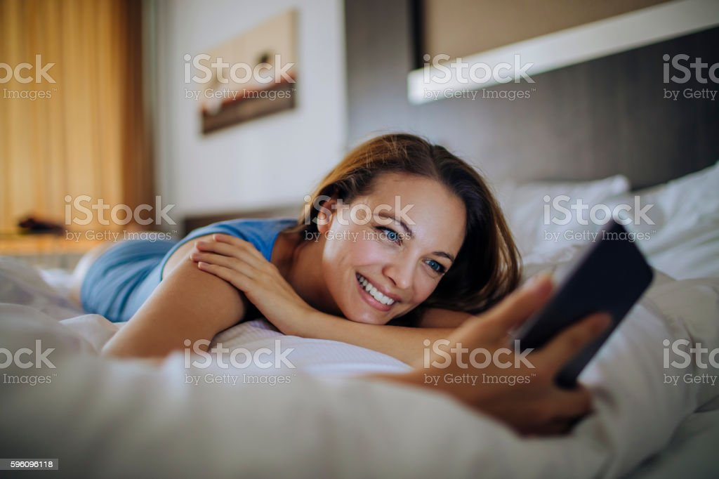 Photo of a young woman laying in bed using smartphone royalty-free stock photo
