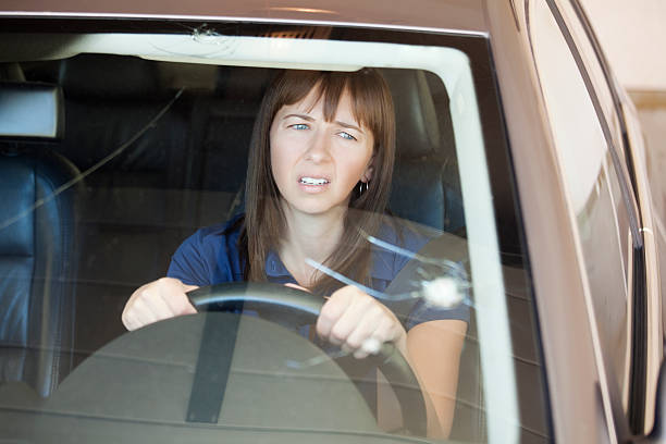 a photo of a young woman looking at crack in her windshield - voorruit stockfoto's en -beelden