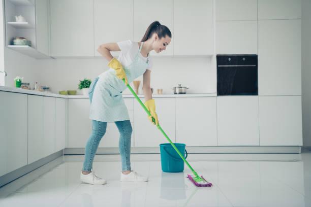 Foto de increíble sorprendente novia apoyando a su madre sobre la limpieza de la cocina mientras ella está acostada en la cama - foto de stock