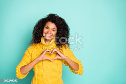 Photo of amazing dark skin lady holding hands in heart figure symbolizing, cardiac health care wear yellow knitted pullover isolated blue teal color background