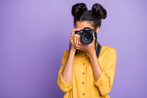Photo Of Amazing Dark Skin Lady Holding Photo Digicam In Hands Photographing Foreign Sightseeing Abroad Wear Yellow Shirt Trousers Isolated Purple Color Background Stock Photo - Download Image Now
