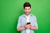 istock Photo of amazing guy holding telephone read new cool instagram post comments overjoyed positive reviews wear denim shirt isolated green color background 1180947086