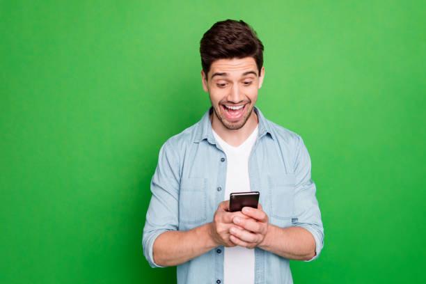 Foto de chico increíble sosteniendo teléfono leer nuevos comentarios frescos instagram post alegríado comentarios positivos usar camisa denim aislado fondo de color verde - foto de stock