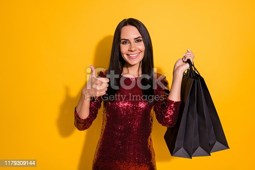 Photo of amazing lady holding packs in hands raising thumb up approving, good prices wear shine red dress isolated yellow color background