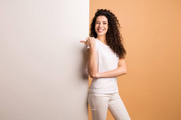 Photo of amazing lady indicating finger on empty discount banner standing near big white placard wear white casual clothes isolated beige pastel color background stock photo
