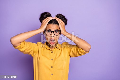 istock Photo of amazing pretty dark skin lady holding hands on head not believe awful bad news open mouth wear specs yellow shirt isolated on purple color background 1181013085