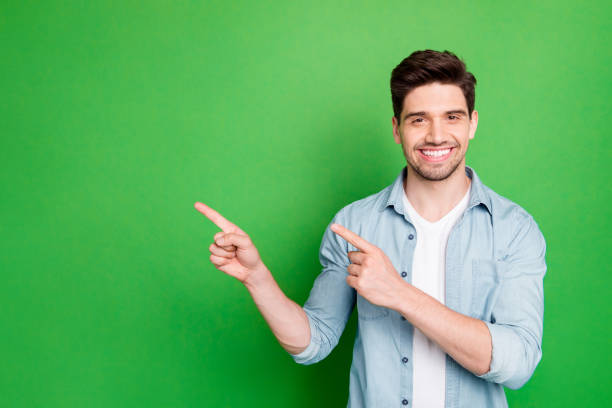 Photo of amazing salesman guy in excited mood indicating finger to empty space advising cool shopping prices wear casual denim shirt isolated green color background stock photo