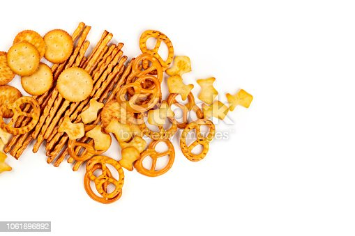 A photo of an assortment of salt crackers, sticks, pretzels, and fishes, shot from the top on a white background with copy space