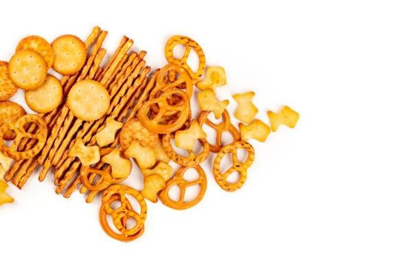 foto's voor een assortiment van zoute crackers, stokken, zoutjes en vissen, een schot vanaf de top op een witte achtergrond met kopie ruimte - snack stockfoto's en -beelden