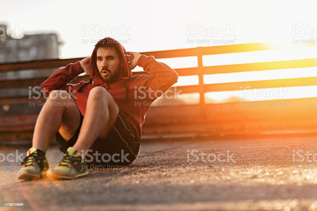 Photo of an athletic young man doing situps stock photo