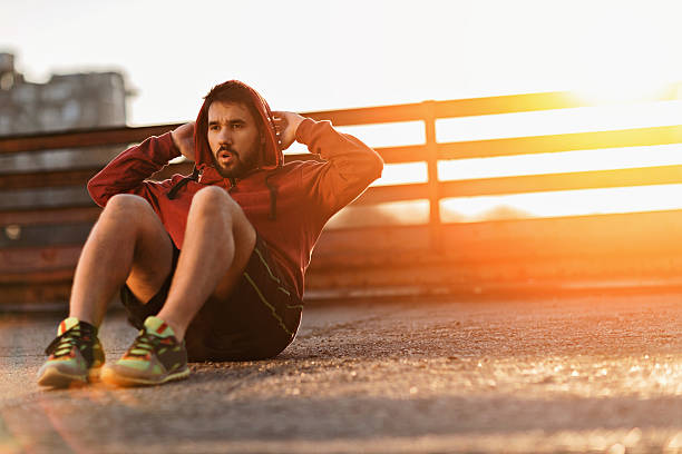 photo of an athletic young man doing situps - sit ups stock photos and pictures