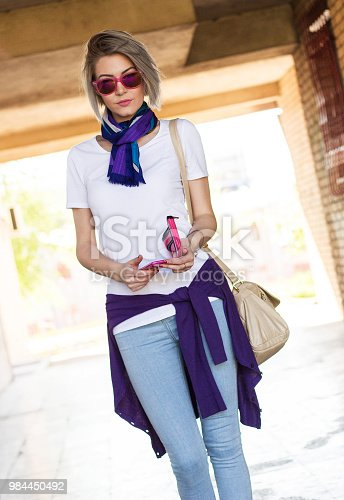 847905020 istock photo photo of an attractive young blonde woman in urban clothing on a sunny summer day using a mobile phone 984450492
