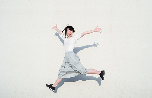Photo of Asian woman jumping with smile in front of white wall.