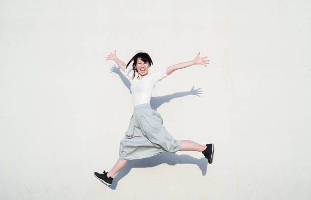 Photo of Asian woman jumping with smile in front of white wall Photo of Asian woman jumping with smile in front of white wall. energetic stock pictures, royalty-free photos & images