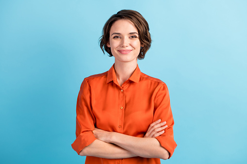 Photo of attractive charming lady cute bobbed hairdo arms crossed, self-confident person worker friendly smile good mood wear orange office shirt isolated blue color background