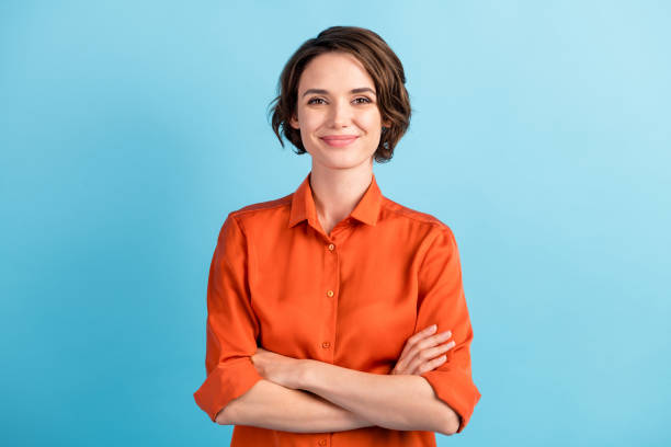 Photo of attractive charming lady cute bobbed hairdo arms crossed self-confident person worker friendly smile good mood wear orange office shirt isolated blue color background stock photo