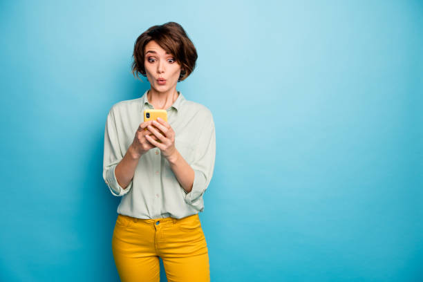 Photo of attractive lady hold telephone hands read new blog post comments not believe eyes speechless wear casual green shirt yellow trousers isolated blue color background stock photo