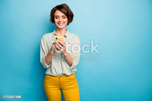 Photo of attractive lady holding telephone hands reading new blog post positive, comments popular blogger wear casual green shirt yellow trousers isolated blue color background