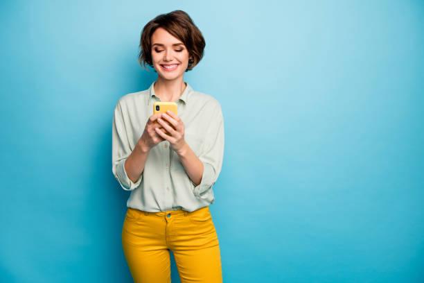foto von attraktiven dame halten telefon hände lesen neuen blog-post positive kommentare beliebte blogger tragen lässige grüne hemd gelbe hose isoliert blau farbe hintergrund - eine frau allein stock-fotos und bilder
