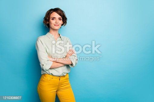 Photo of attractive pretty business lady short hairstyle friendly smiling, responsible person arms crossed wear casual green shirt yellow pants isolated blue color background