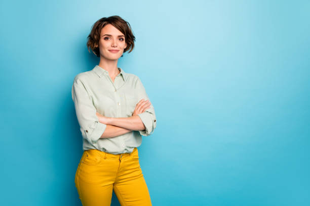 Photo of attractive pretty business lady short hairstyle friendly smiling responsible person arms crossed wear casual green shirt yellow pants isolated blue color background Photo of attractive pretty business lady short hairstyle friendly smiling, responsible person arms crossed wear casual green shirt yellow pants isolated blue color background background color stock pictures, royalty-free photos & images