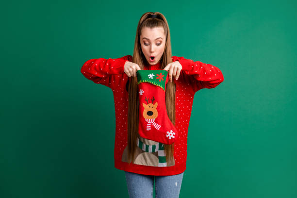 Photo of attractive shocked lady hold newyear stocking x-mas present family tradition look inside open mouth long-waited gift wear red ugly ornament pullover isolated green color background stock photo