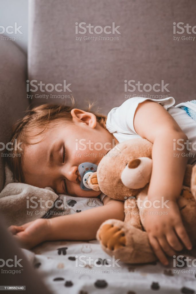 Baby sleeping on sofa. Peaceful baby lying on a bed while sleeping in...