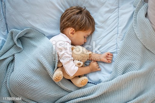 Photo of baby boy sleeping together with teddy bear. His favorite napping spot. Adorable kid boy after sleeping in bed with toy. Boy sleeping on bed with teddy bear. Sleepyhead