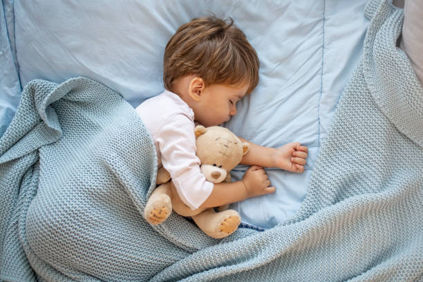 Photo of baby boy sleeping together with teddy bear. Photo of baby boy sleeping together with teddy bear. His favorite napping spot. Adorable kid boy after sleeping in bed with toy. Boy sleeping on bed with teddy bear. Sleepyhead teddy bear stock pictures, royalty-free photos & images