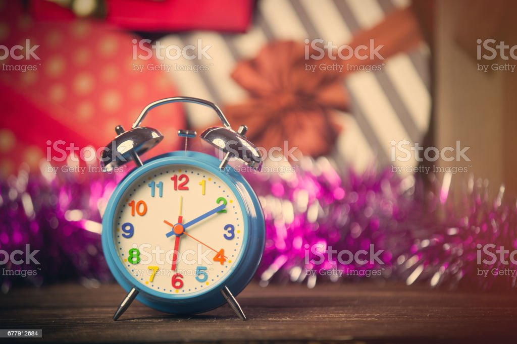 photo of beautiful alarm clock on the wonderful gifts and garland background royalty-free stock photo