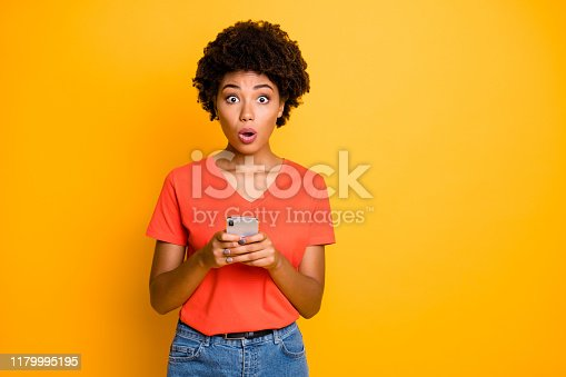 Photo of beautiful attractive cute charming girlfriend scared with something, afro american chatting wearing jeans denim t-shirt isolated over yellow vivid color background