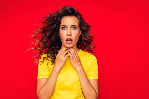 Photo of beautiful girl with curly hairstyle posing on red background