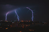 Photo of beautiful powerful lightning over big city, zipper and thunderstorm, abstract background, dark blue sky with bright electrical flash, thunder and thunderbolt, bad weather concept