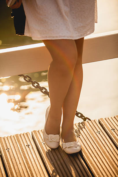 photo of beautiful woman legs in ballet flats on bridge - flat shoe stock photos and pictures