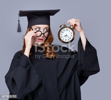 istock photo of beautiful young alumnus with alarm clock on the wonderful grey studio background 677928752