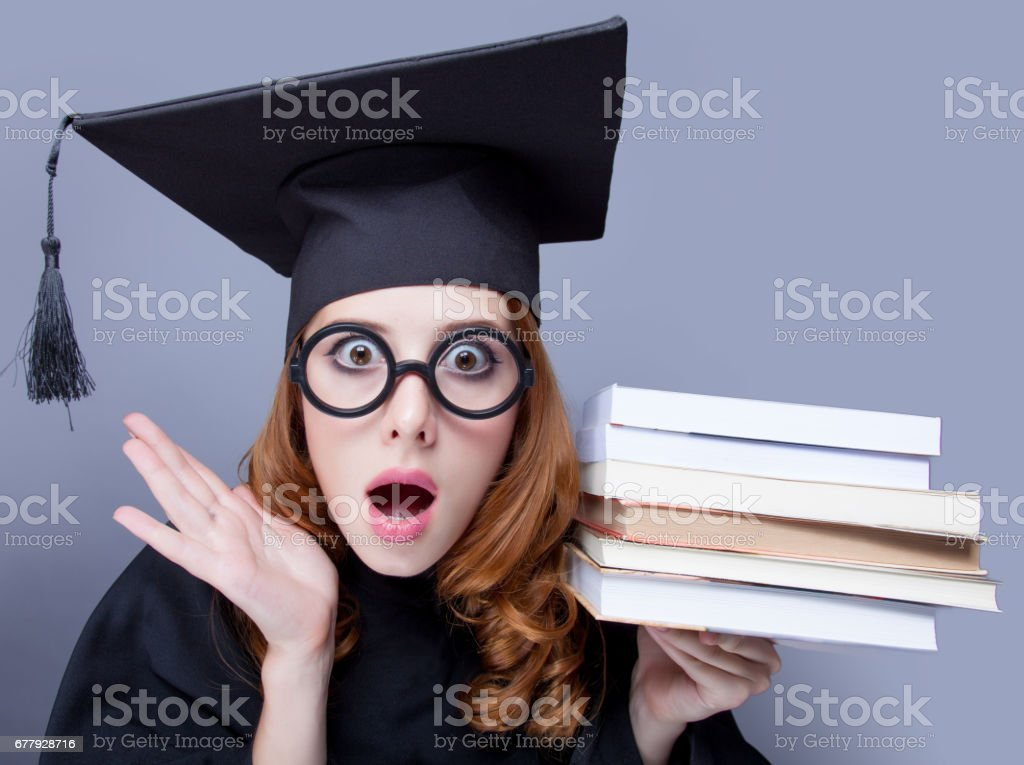 photo of beautiful young alumnus with pile of books on the wonderful grey studio background royalty-free stock photo