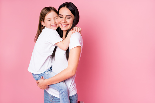 Photo of beautiful young mother hold arms little daughter two ladies hugging best friends lovely feelings eyes closed wear casual t-shirts jeans isolated pastel pink color background