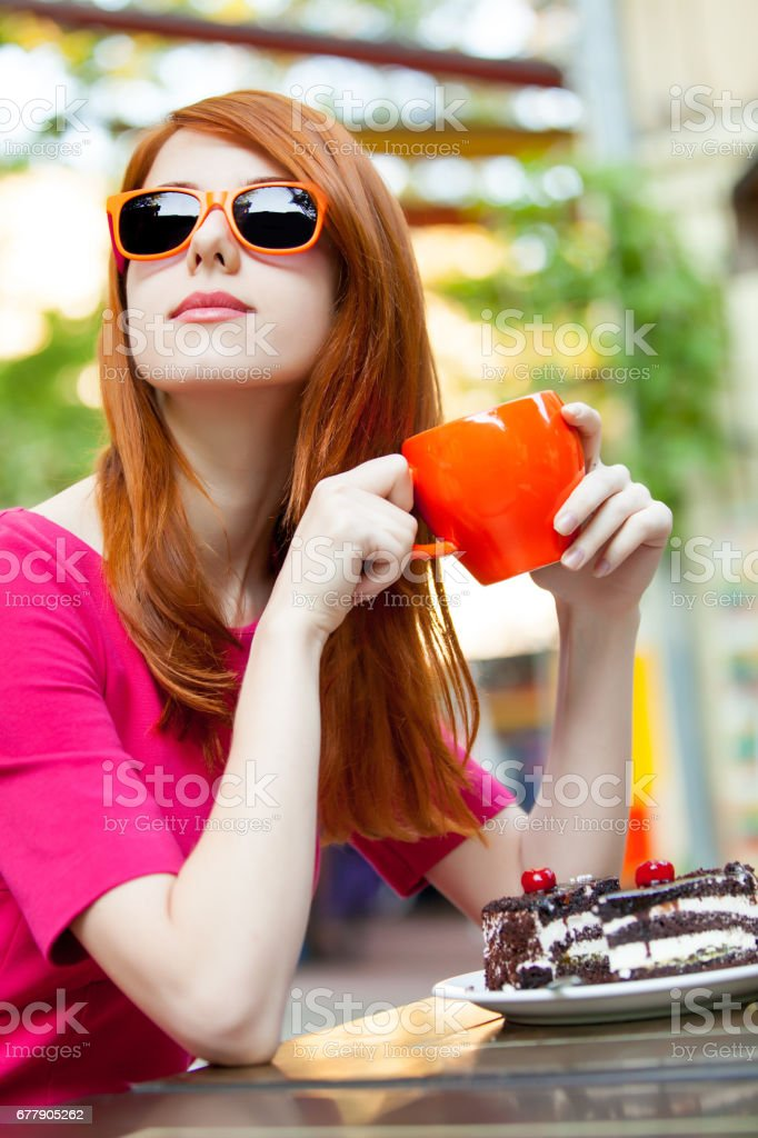 photo of beautiful young woman eating chocolate cake and drinking coffee in the cafe royalty-free stock photo