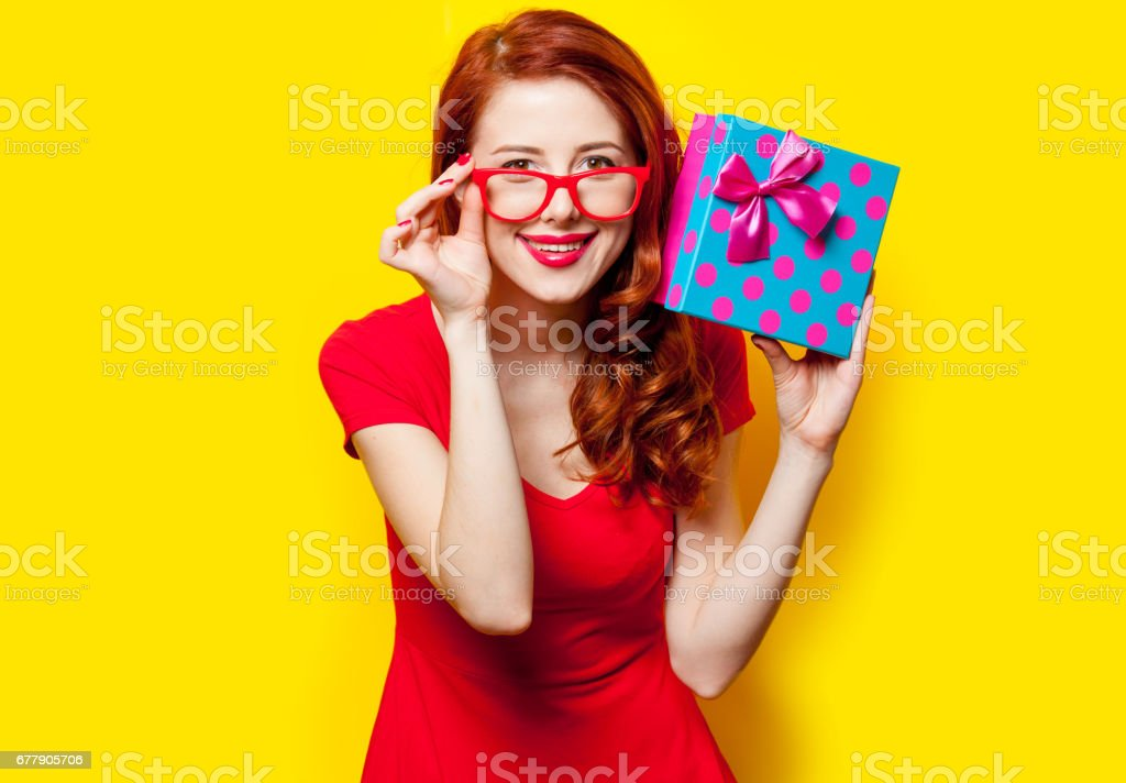 photo of beautiful young woman holding cute gift on the wonderful yellow studio background royalty-free stock photo