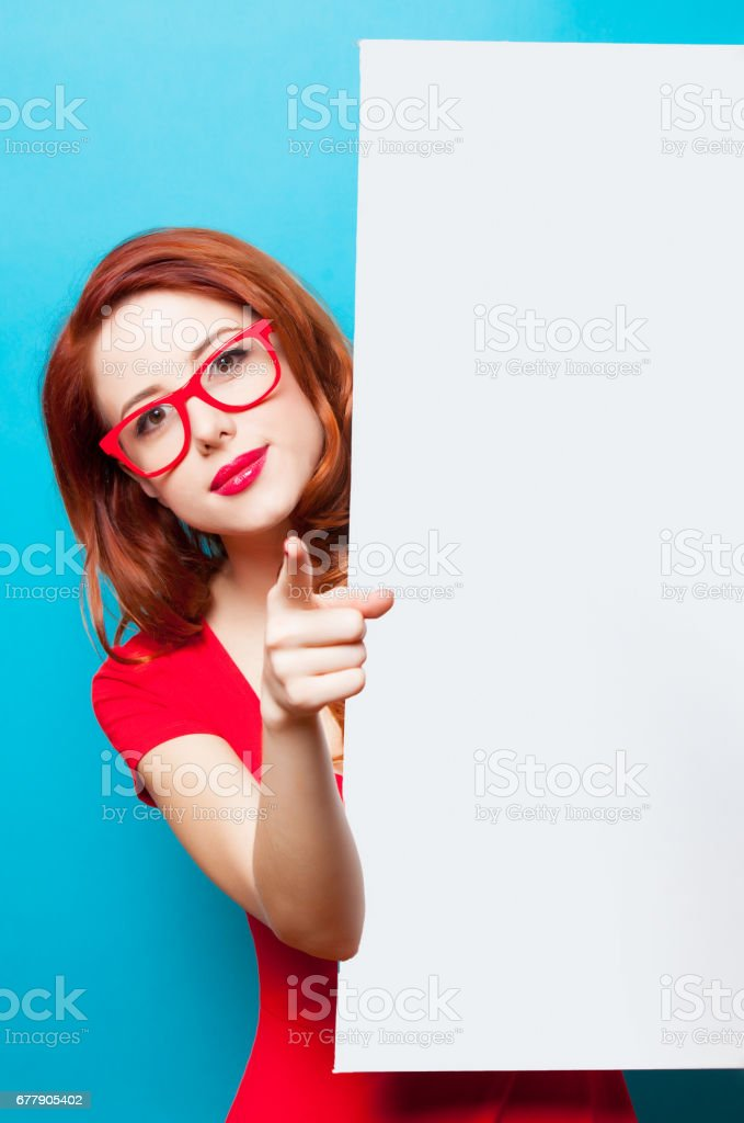 photo of beautiful young woman holding empty poster on the wonderful blue studio background royalty-free stock photo