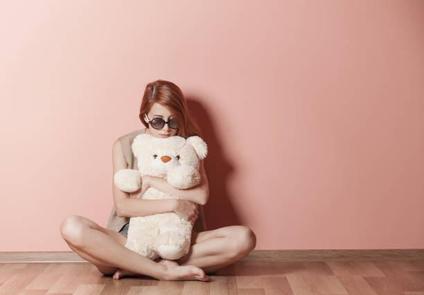 photo de la belle jeune femme étreignant l'ours en peluche et s'asseyant près du mur - doudou photos et images de collection