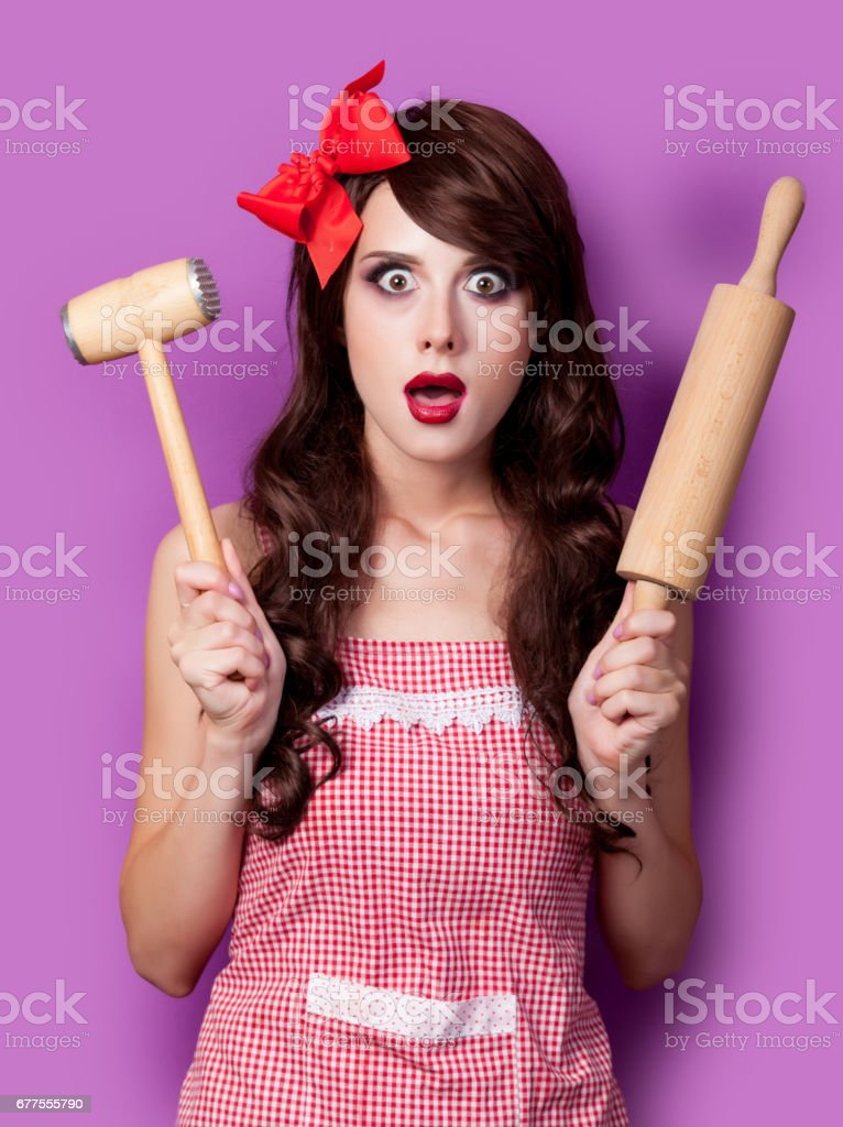photo of beautiful young woman in apron with rolling pin and hammer on the wonderful purple background royalty-free stock photo