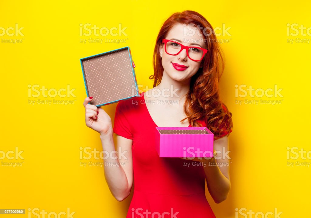 photo of beautiful young woman opening cute gift on the wonderful yellow studio background royalty-free stock photo