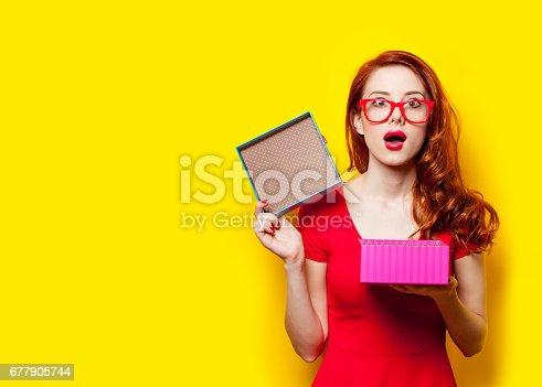 istock photo of beautiful young woman opening cute gift on the wonderful yellow studio background 677905744