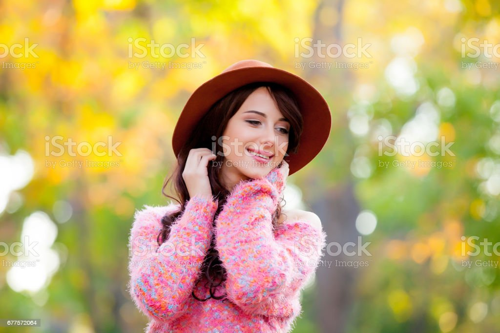 photo of beautiful young woman standing in the park and smiling royalty-free stock photo