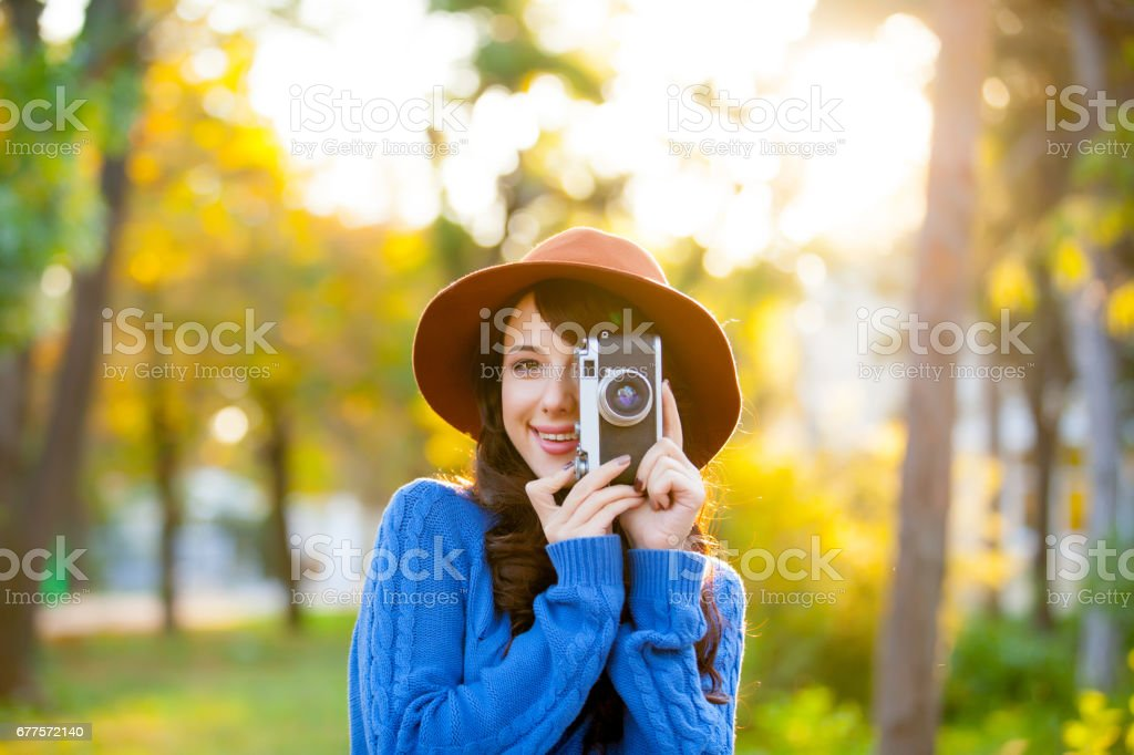 photo of beautiful young woman standing in the park with retro camera royalty-free stock photo