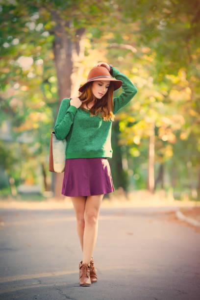 foto von schönen jungen frau stehen auf dem wunderbaren herbstpark hintergrund - damen rock braun stock-fotos und bilder