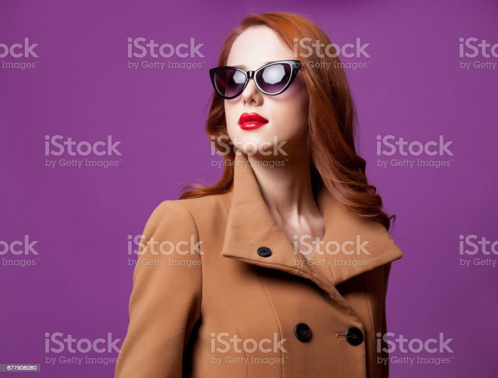 photo of beautiful young woman standing on the wonderful purple studio background royalty-free stock photo