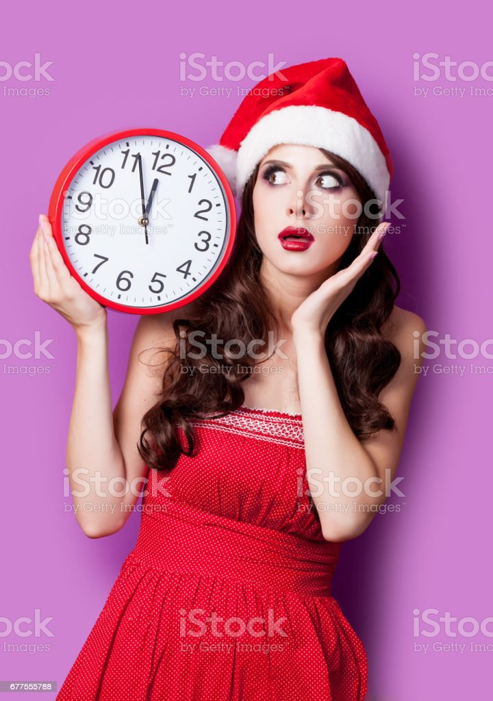 photo of beautiful young woman with clock in santa claus hat on the wonderful purple background royalty-free stock photo